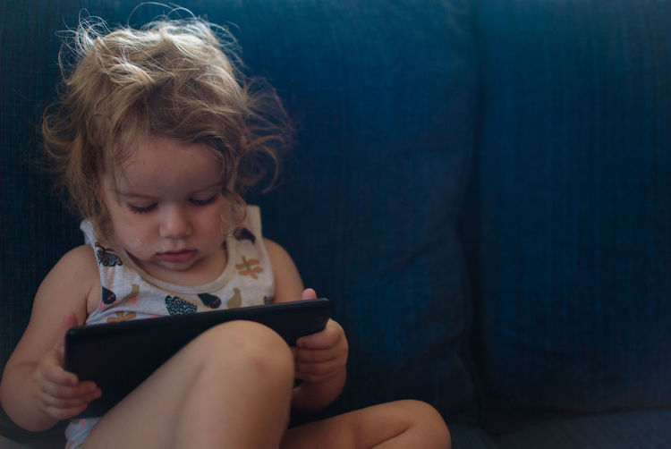 Close-up of girl using digital tablet at home
