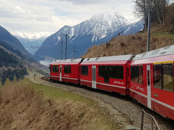 Train on snowcapped mountains against sky