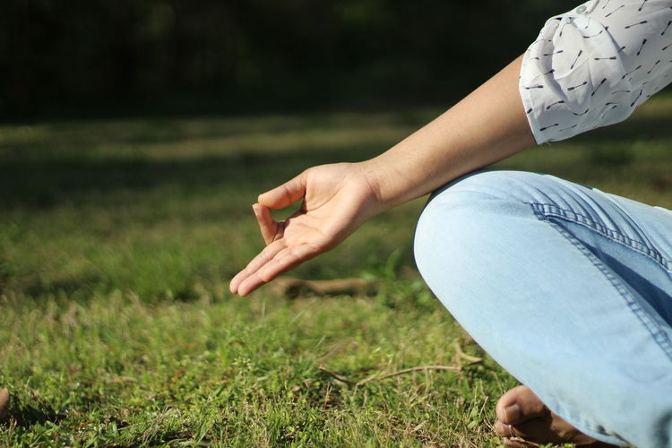 Midsection of woman doing yoga on field