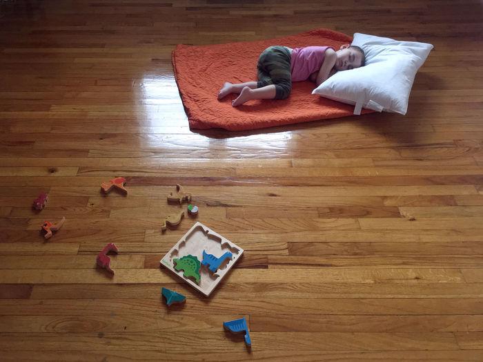 High angle view of baby lying on hardwood floor at home