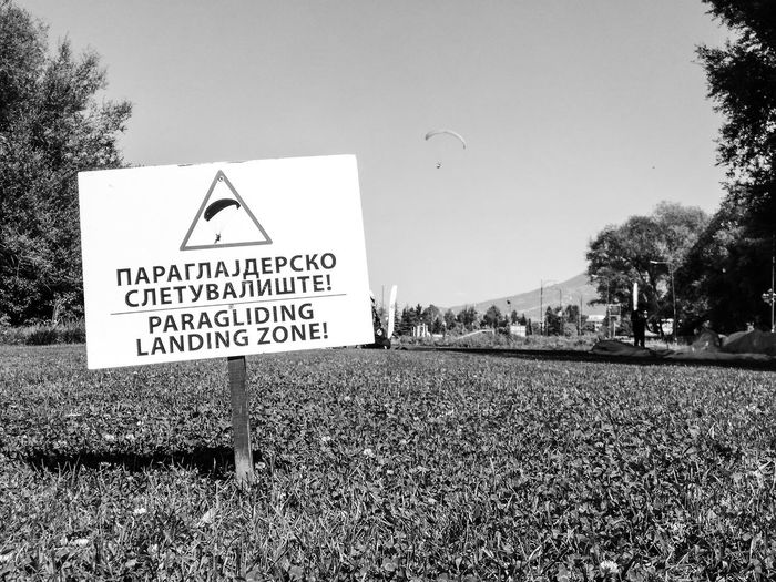 Black & White Grass Landing Paragliding Sign Animal Themes Black And White Blackandwhite Clear Sky Communication Day Grass Nature No People Outdoors Road Sign Sky Text Tree Warning Sign