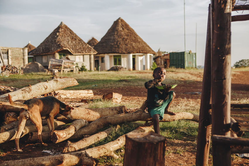 Africa African Boy Child Childhood Dog Domestic Animals Eating Evening Light Food Huts Meal Mpigi Outdoors Poor  Poverty Real People Rural Rural Scene Simple Things In Life Sina Sitting Social Business Thatched Roof Wood - Material
