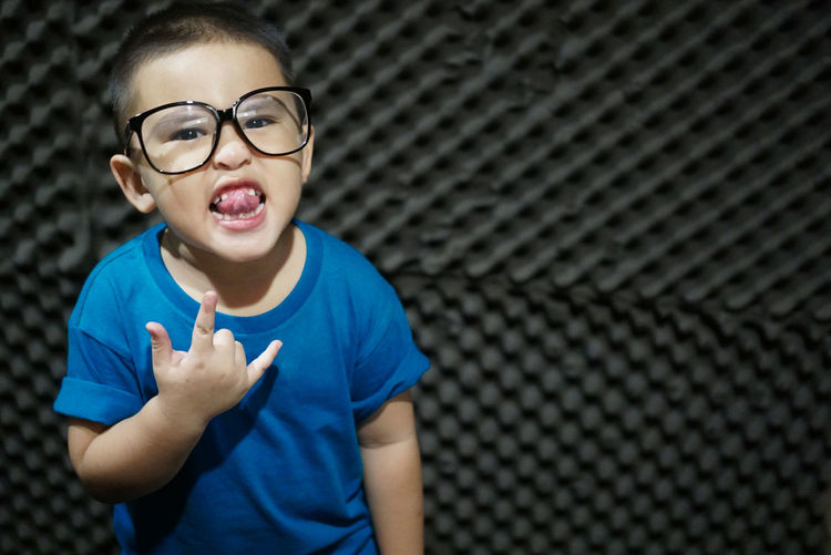 Portrait of boy sticking out tongue while gesturing horn sign