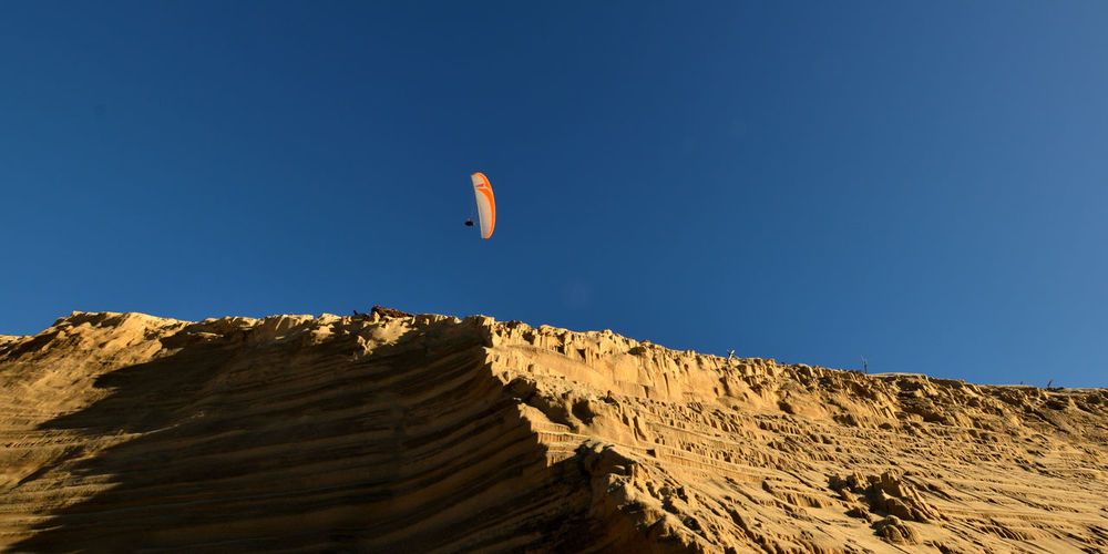 Person Paragliding Against Clear Blue Sky
