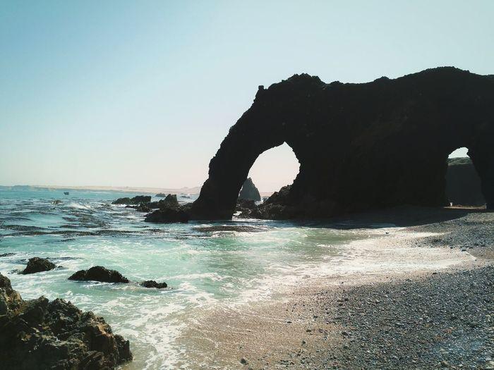 Rock formation on beach against clear sky