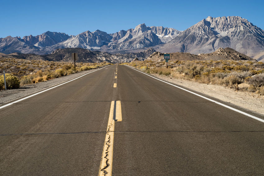 road heading toward Eastern Sierra Nevada mountains, White mountain range, and Inyo National Forest, Bishop, California, USA Mountain Road Direction The Way Forward Sign Mountain Range Transportation Scenics - Nature Symbol Road Marking Marking Diminishing Perspective Beauty In Nature Nature No People Day Environment Arid Climate Outdoors Eastern Sierras California Inyo National Forest