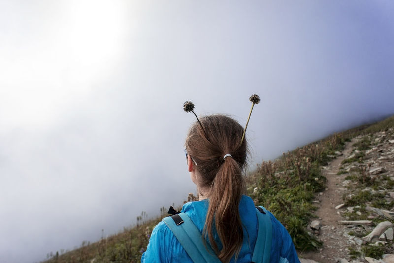 Girl from the back with plant horns on her head in fog in mountains. fun concept, hiking