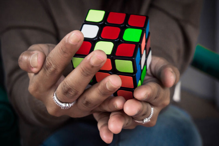 Midsection of woman holding puzzle cube