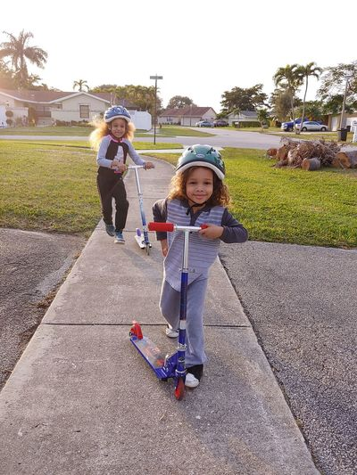 Portrait of smiling girls riding push scooters on footpath