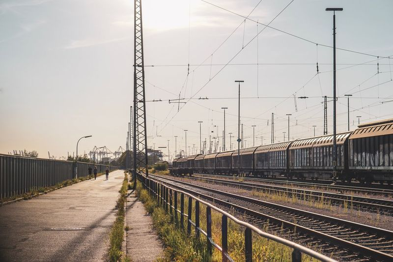 Train On Railroad Tracks Against Sky During Sunny Day