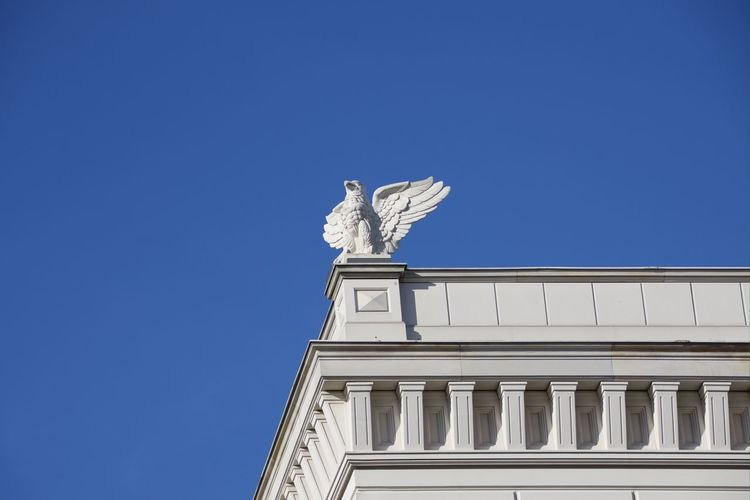 Low angle view of statue against building against clear blue sky