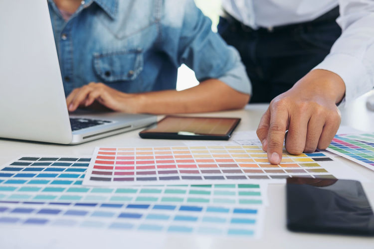 Midsection of design professionals with laptop and color swatches on office desk