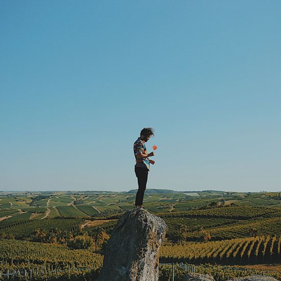 Man Holding Drink While Standing On Rock At Field Against Clear Sky