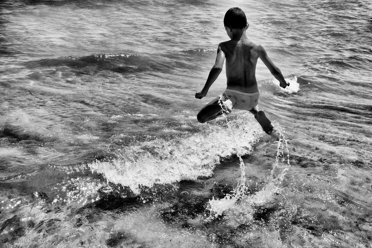 Rear view of shirtless child in sea