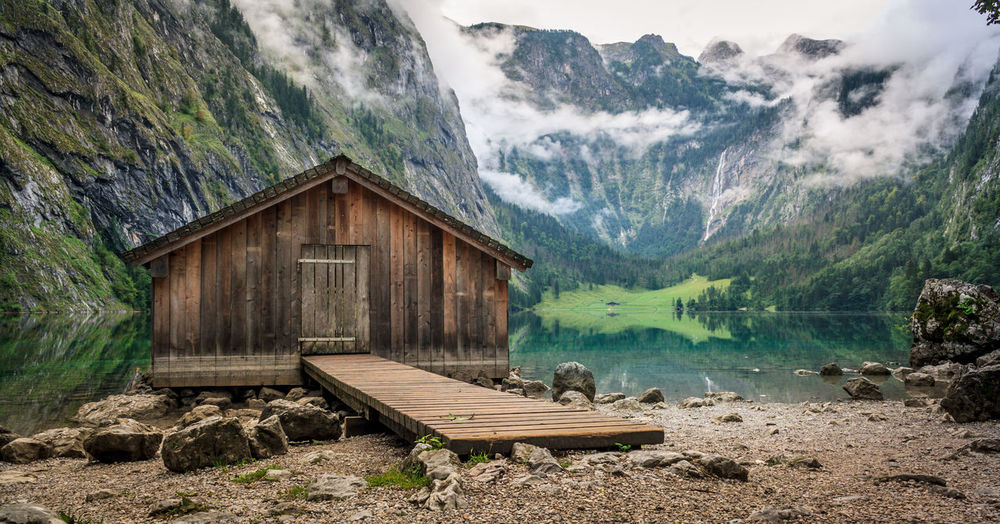 Log Cabin By Obersee Lake Amidst Mountain During Foggy Weather
