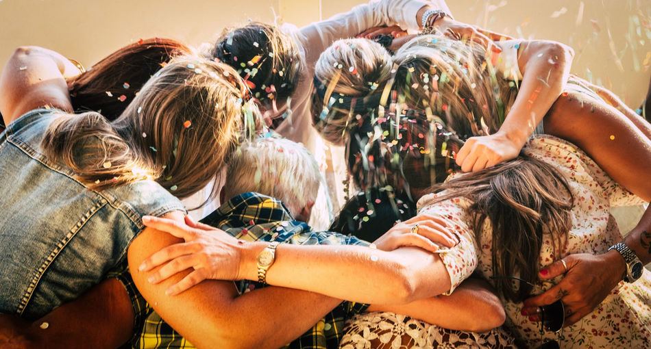 Group of people huddling while partying at home