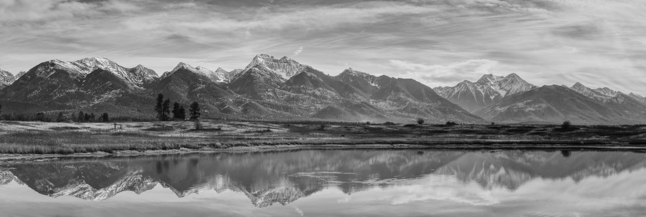 Panorama of a Montana mountain range reflected in a lake in black and white. Mountain Scenics - Nature Water Beauty In Nature Reflection Mountain Range Lake Cloud - Sky Sky Tranquility Landscape Environment Tranquil Scene Nature No People Non-urban Scene Day Idyllic Panoramic Outdoors Snowcapped Mountain Majestic Panoramic Panoramic Photography Panoramic View Panoramic Landscape Panorama Montana