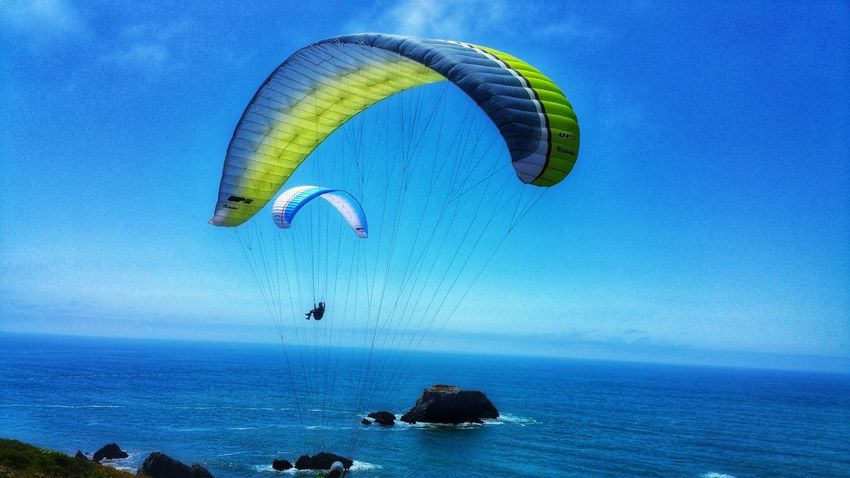 Convergence. Paragliding duo. Jumping off cliffs. Gliding over the ocean. Yellow Hite Adventure Thrill Extreme Sports Sport Gray Background Converge Merging Zen Timeless Copy Space Distance Shimmering Cliffs Danger Paragliding Parachute Sea Flying Adventure Water Extreme Sports Blue Mid-air Sky Coast Gliding Kite