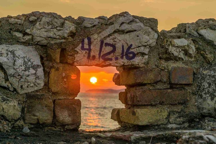 Stone wall by sea against sky during sunset