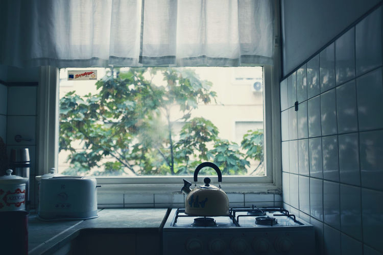 Teapot on stove by window at home