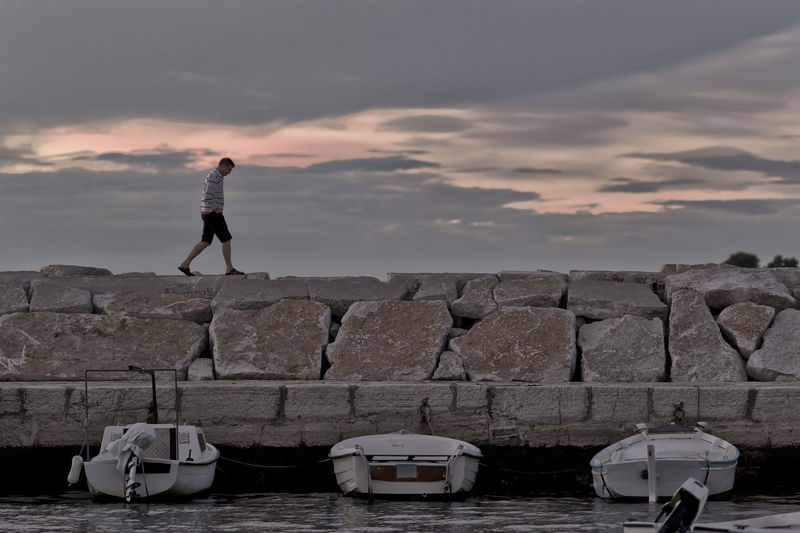 Side view of man walking on retaining wall by sea against cloudy sky during sunset