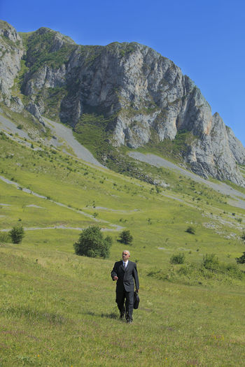 Businessman walking in nature in front of rocky mountains. Adventure Club Business Transylvania Trascau Mountains Adventure Business Concept Businessman Businessperson Grass Landscape Leisure Activity Lifestyles Mountain Mountain Range Nature One Person Outdoors person Real People Rocky Mountains Scenics
