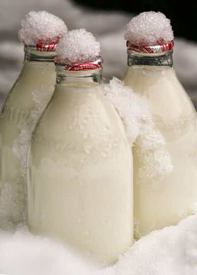 Close-Up Of Milk Bottles On Snow Covered Field During Winter