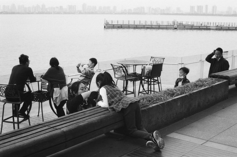 Group of people sitting on railing against calm water