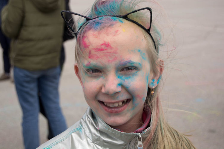 Portrait of smiling girl face covered with powder paint during holi