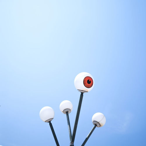 Electric Lamp Blue Background Sphere Connection Close-up Sunlight Outdoors White Color Electricity  Street Day Communication Nature Clear Sky No People Copy Space Low Angle View Street Light Technology Sky Blue Lighting Equipment Electricity  Cut Out Metal