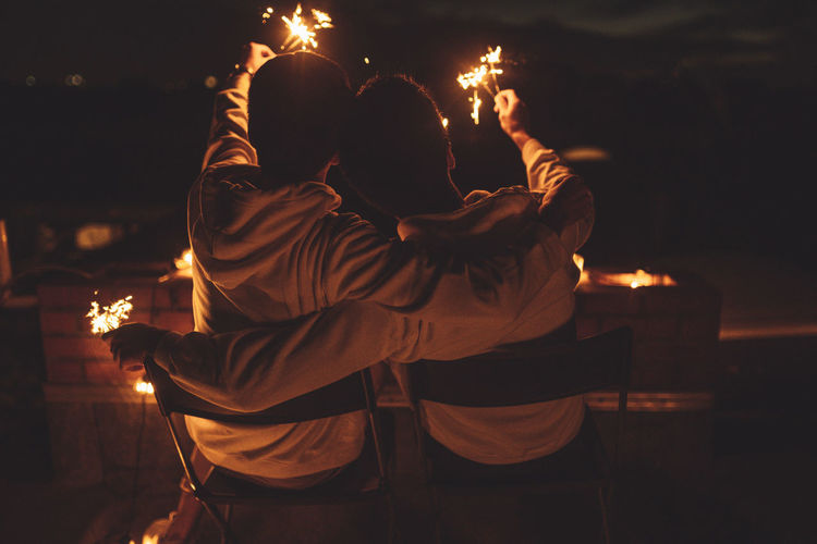 Man and woman with fire crackers at night