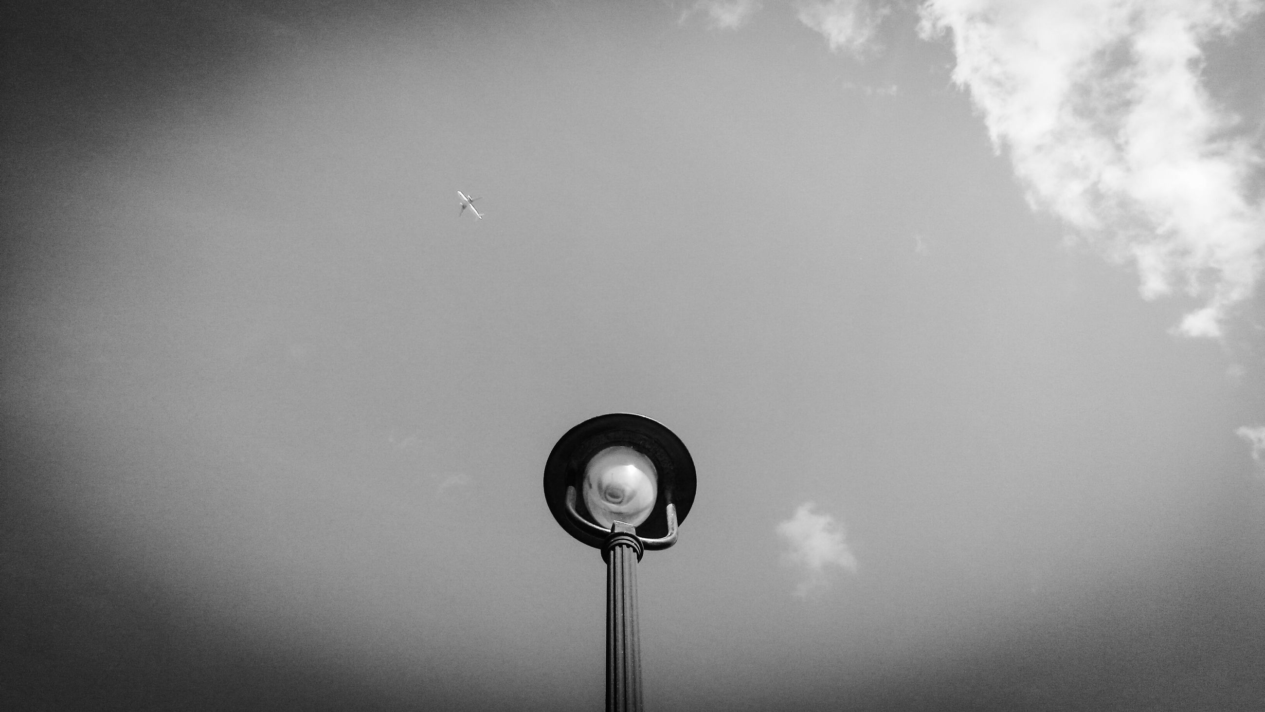 low angle view, street light, lighting equipment, sky, electricity, technology, electric light, cloud - sky, lamp post, built structure, no people, outdoors, day, nature, cloud, pole, high section, cloudy, silhouette, copy space