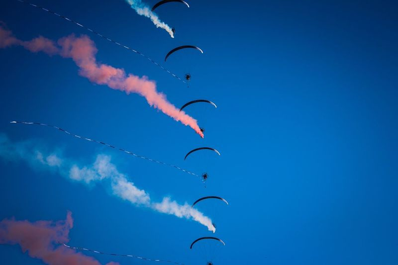 Low angle view of people paragliding against clear blue sky during sunny day