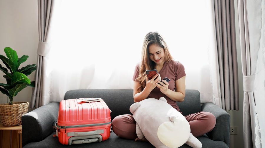 Smiling woman online shopping though mobile phone at home