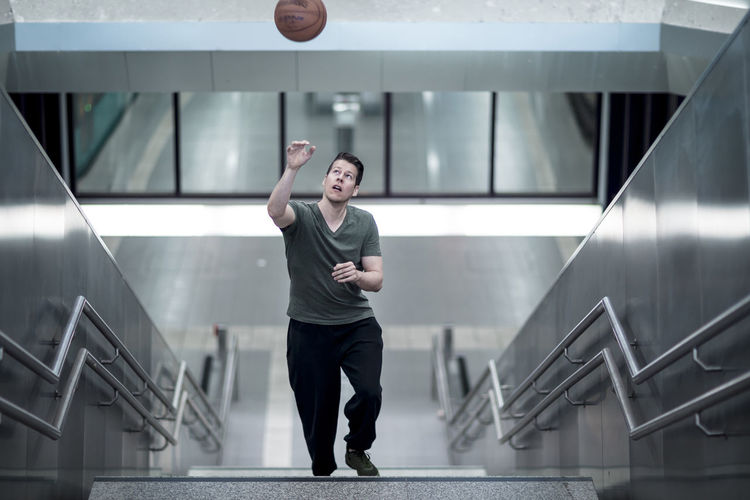 High Angle View Of Young Man Playing With Basketball Moving Up On Steps