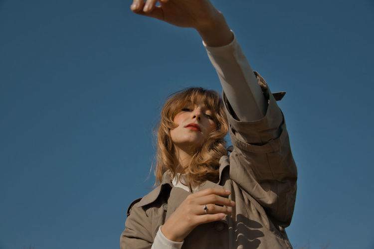 Low angle view of woman against clear blue sky