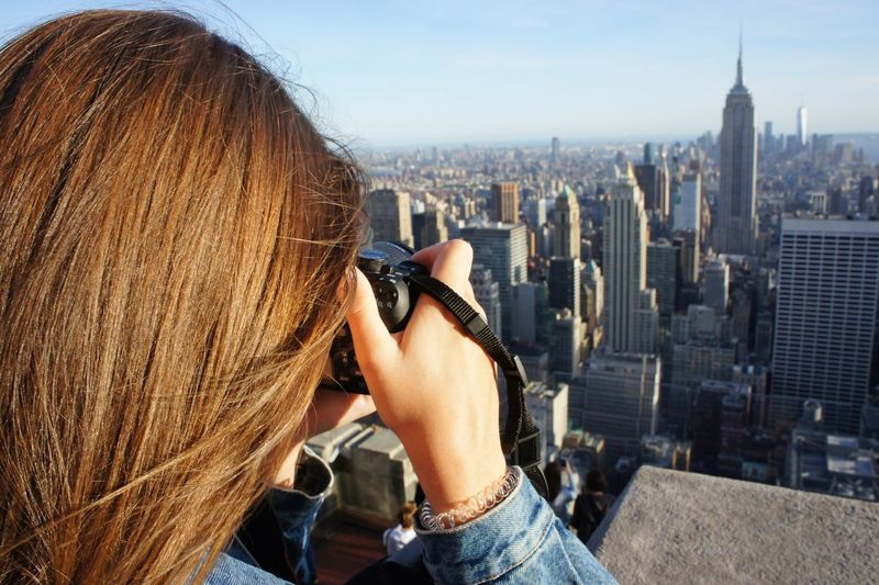 Rear view of woman photographing cityscape