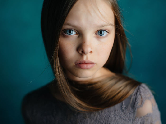 Close-up portrait of girl against blue background
