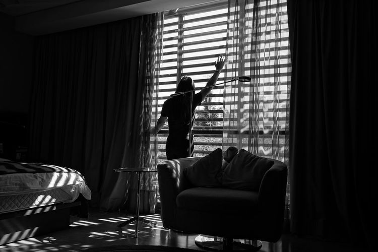 Rear view of man standing by window on sofa at home