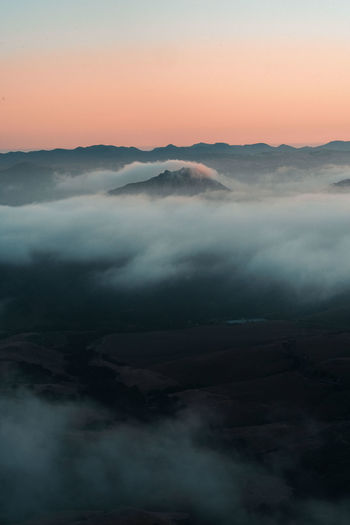 Scenic view of mountains shrouded in clouds against sky during sunset
