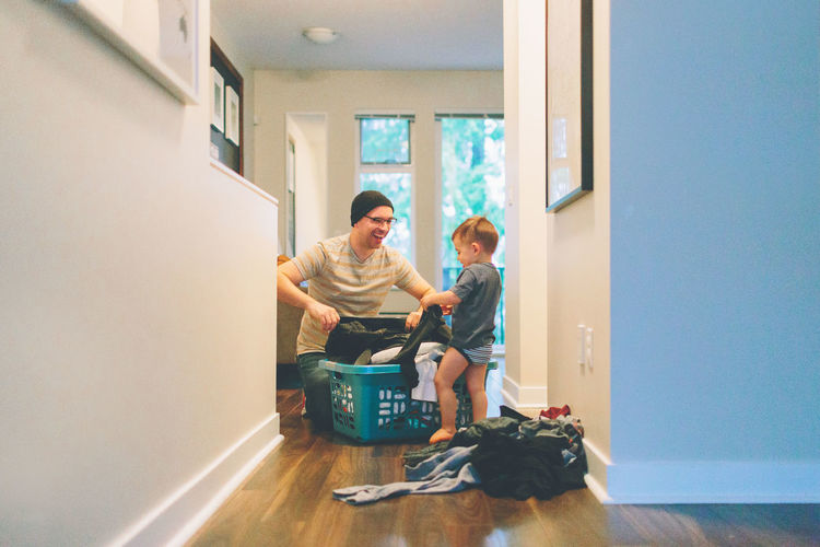 Father And Son Holding Laundry At Home
