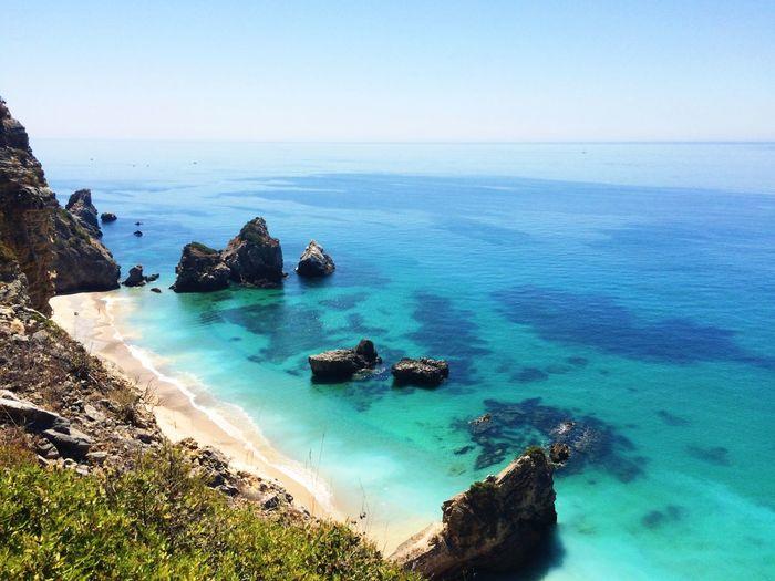 Scenic View Of Praia Do Ribeiro Do Cavalo Against Clear Sky
