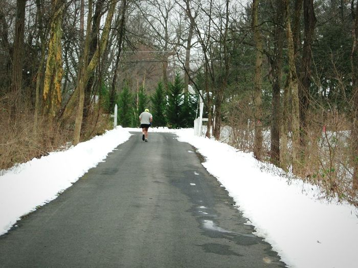 Rear View Of Man Jogging On Country Road Amidst Snow