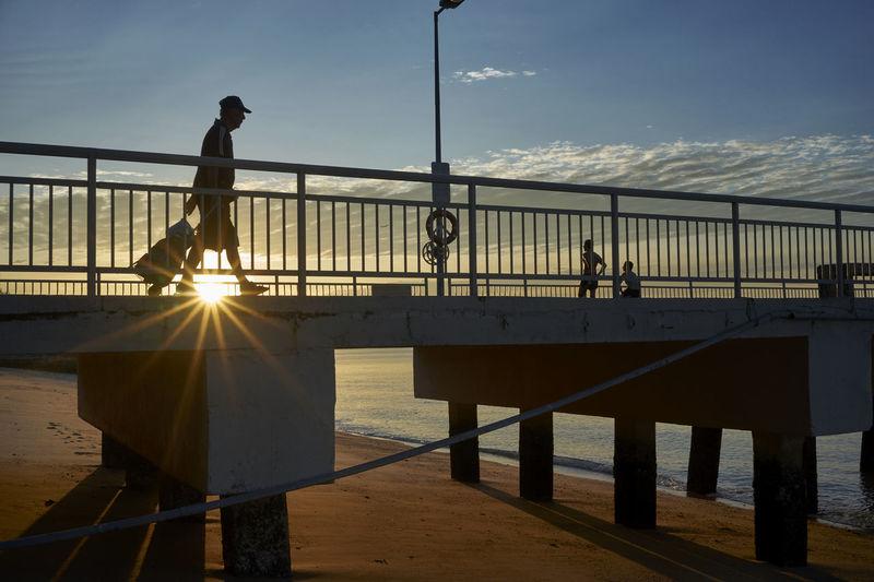 Silhouette of person crossing Bedok Jetty during sunrise Bedok Jetty Bridge Bridge - Man Made Structure Jetty Men Outdoors Railing Railings Sea Silhouette Singapore Sky Street Street Photography Sun Sunbeam
