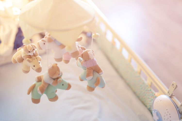 High angle view of toys hanging in crib at home