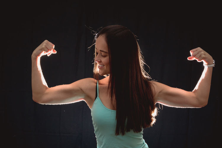 Smiling woman flexing muscles while standing against black background
