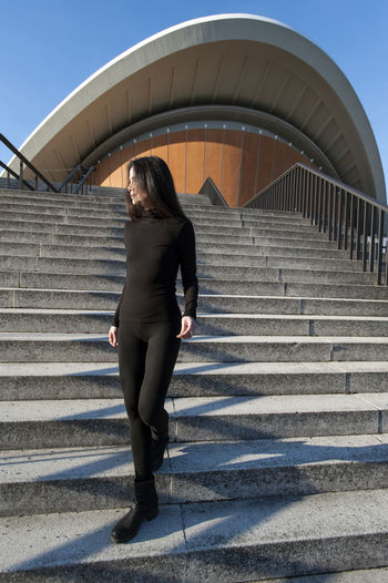 Full length of young woman moving down on steps