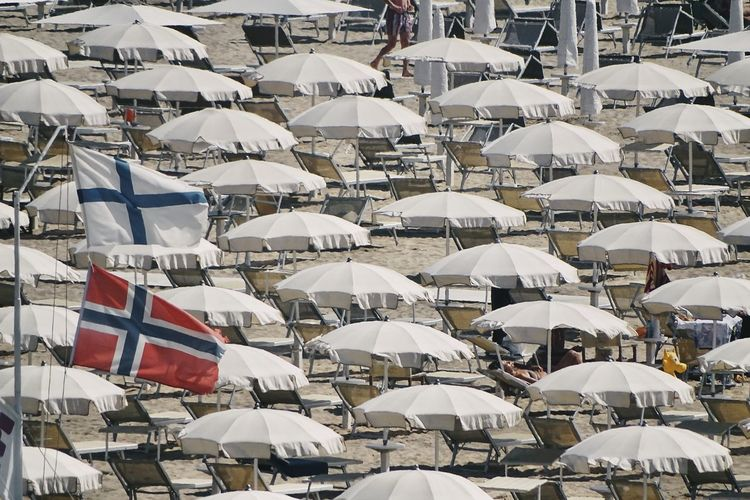 Low angle view of flags against beach umbrellas