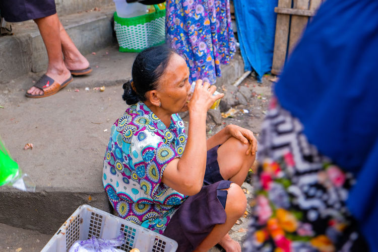 High angle view of woman drinking juice sitting at market