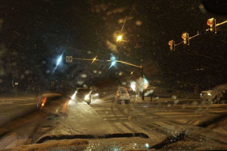 The challenge of winter driving. On the road in a snowstorm. Cars Driving Hazardous Illuminated Intersection Night Outdoors Poor Visibility Road Road Hazards Slippery Snow Snowfall Snowing Stoplight Street Streetlights Transportation Windshield Winter Weather Ice